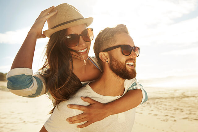 Young couple with sunglasses smiling on a beach.