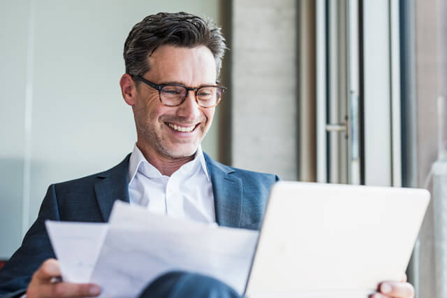 Businessman with glasses smiling and using a laptop.