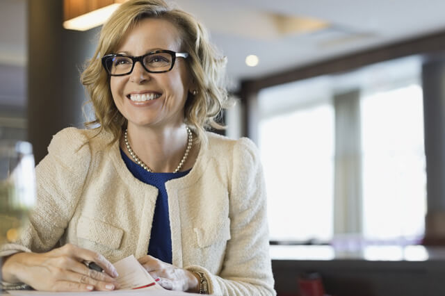 A smiling businesswoman with glasses.