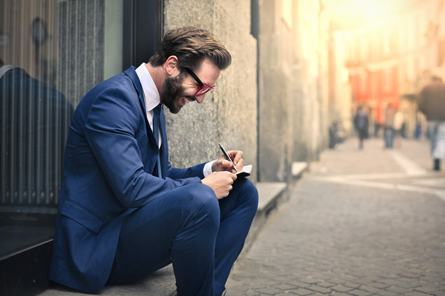 A young businessman sits outside, smiling and taking notes.