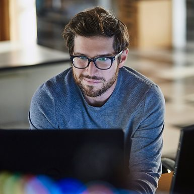 Young man with glasses looking at a computer.