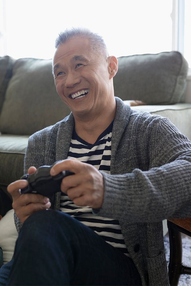 Middle aged man playing a video game and smiling.