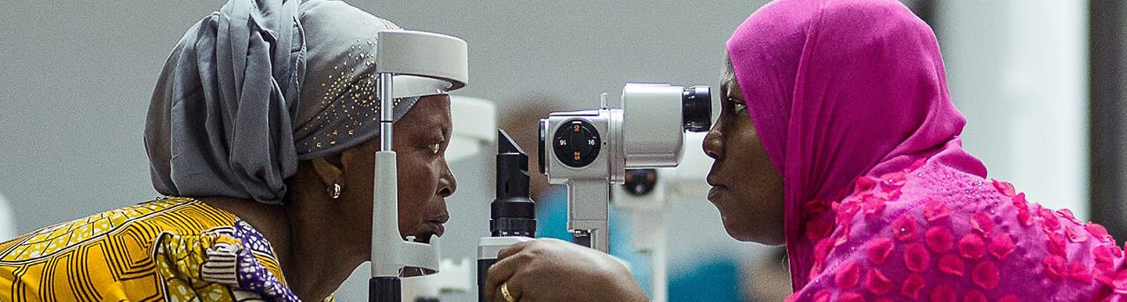 A woman examines another woman's eyes using a slit lamp.