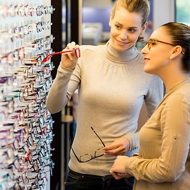 Two women looking at a large variety of glasses.