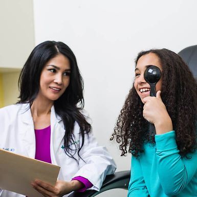 An optometrist administering a vision test for a young girl.