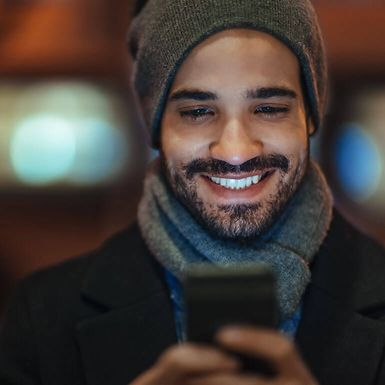 Young man in winter attire uses a smartphone.