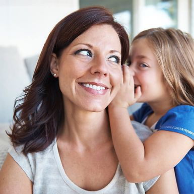 A young girl whispering in her mother's ear