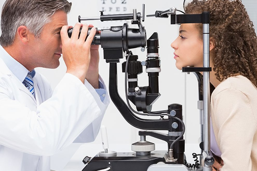 An eye doctor performs an eye exam on a young woman