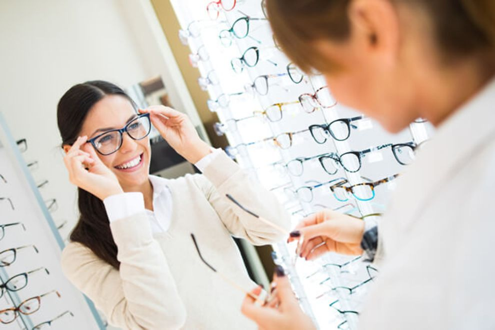 woman trying on glasses in an eye doctor's office