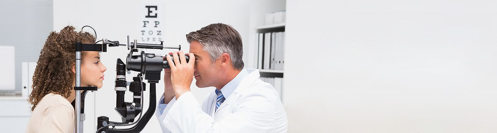 An eye doctor examines a patient's eyes