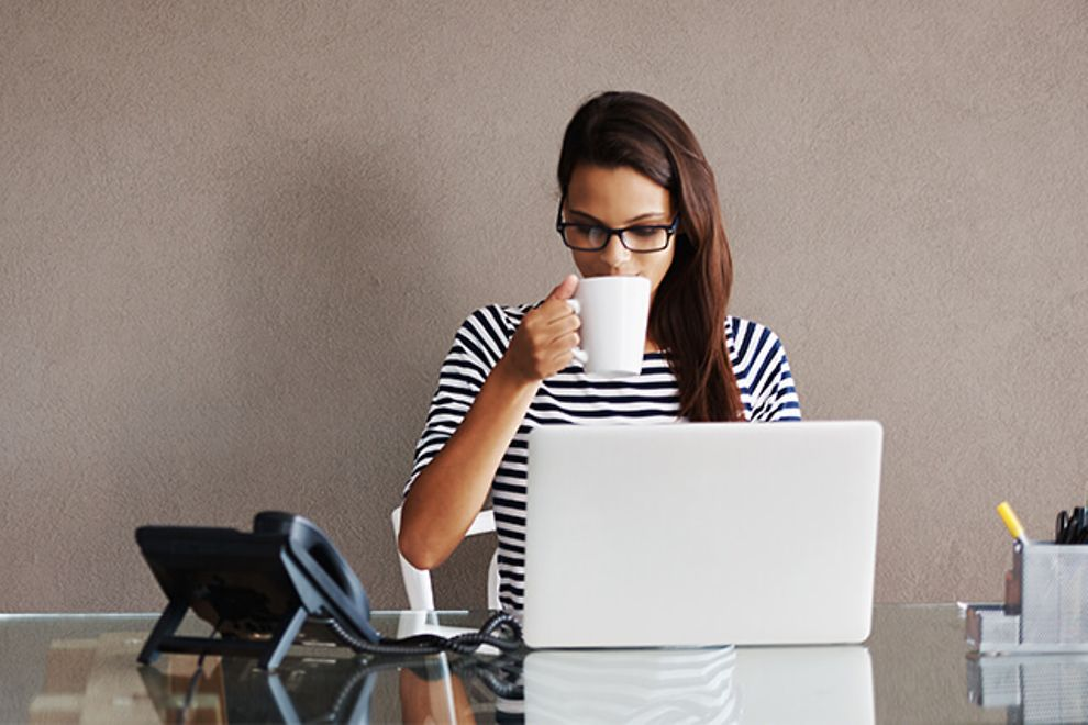 Young professional woman sips coffee at her desk
