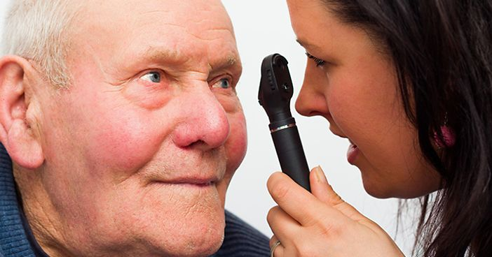 An eye doctor examining an older man's eye