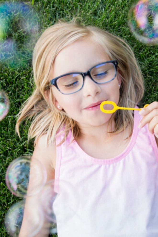 A young girl laying in grass, blowing bubbles from a wand.